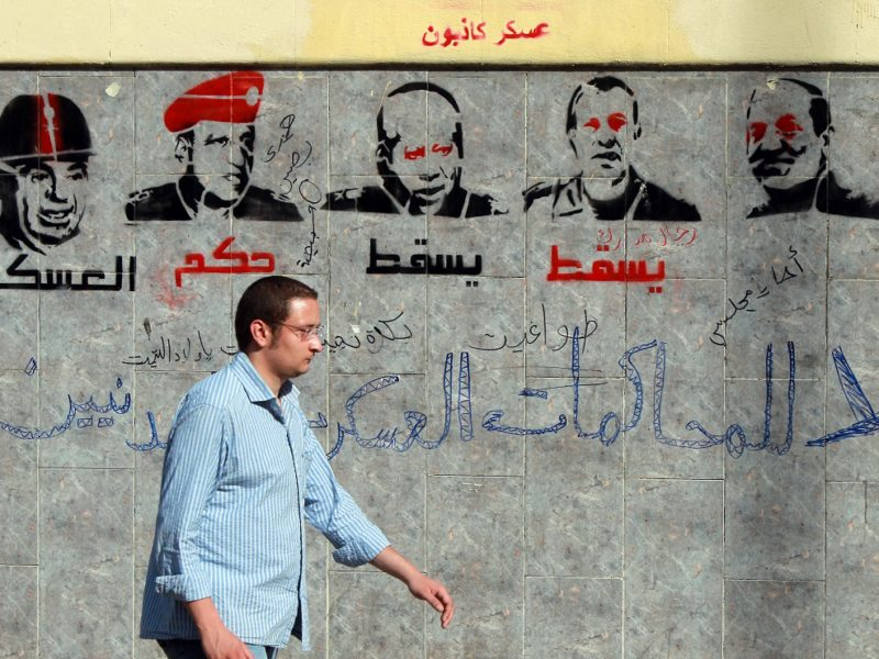 "An Egyptian man walks past graffiti depicting members of the military council and reading ""Down with the military rule, no to military trials for civilians"" near the defence ministry in the Abbassiya district of Cairo on April 29, 2012. The first round of post-revolution presidential election is scheduled for May 23 and 24, and the interim military leadership has promised to hand power to an elected civilian president by the end of June. AFP PHOTO/KHALED DESOUKI        (Photo credit should read KHALED DESOUKI/AFP/GettyImages)"