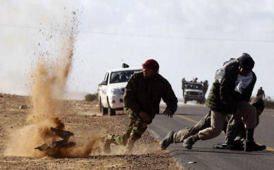 Rebel fighters jump away from shrapnel during heavy shelling by forces loyal to Libyan leader Muammar Gaddafi near Bin Jawad, March 6, 2011. Rebels in east Libya regrouped on Sunday and advanced on Bin Jawad after forces loyal to Muammar Gaddafi ambushed rebel fighters and ejected them from the town earlier in the day.  REUTERS/Goran Tomasevic (LIBYA - Tags: POLITICS CIVIL UNREST IMAGES OF THE DAY)